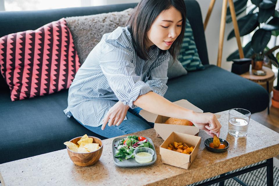 High angle view of young woman eating takeaway food, sitting on the couch at home.