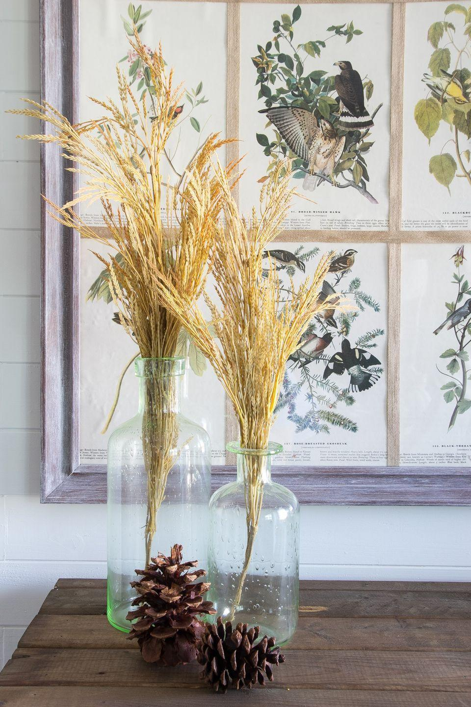 """<p>To decorate around art without distracting from it, swap bright blooms for simple wheat stalks, as in this <a href=""""https://www.elledecor.com/life-culture/entertaining/g2660/fall-centerpieces/"""" rel=""""nofollow noopener"""" target=""""_blank"""" data-ylk=""""slk:autumn decor"""" class=""""link rapid-noclick-resp"""">autumn decor</a> from <a href=""""http://www.blesserhouse.com/2015/09/2015-fall-home-tour-part-two.html"""" rel=""""nofollow noopener"""" target=""""_blank"""" data-ylk=""""slk:Bless'er House"""" class=""""link rapid-noclick-resp"""">Bless'er House</a>. </p>"""