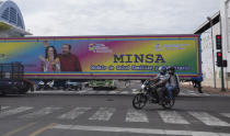 A motorcyclist rides past a truck billboard promoting President Daniel Ortega and his wife and Vice President Rosario Murillo, in Managua, Nicaragua, Thursday, June 17, 2021. In recent weeks, Nicaragua President Daniel Ortega's government has rounded up 13 opposition leaders, including four presidential challengers for the Nov. 7 elections. They face allegations ranging from money laundering to crimes against the state. (AP Photo/Miguel Andres)