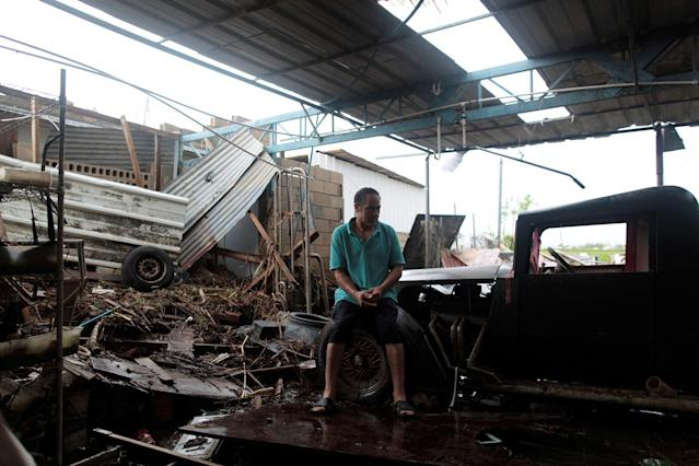 <p>Freddy Guerrero sits amidst the remains of his auto shop, after the island was hit by Hurricane Maria in Toa Baja, Puerto Rico, Oct. 16, 2017. (Photo: Alvin Baez/Reuters) </p>