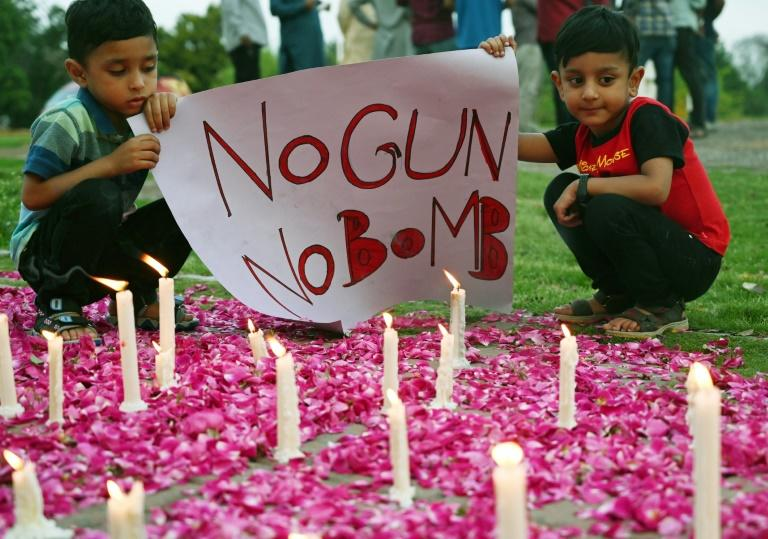 Pakistani children hold a placard next to candles during a vigil to pay tribute to the Sri Lankan blasts victims, in Islamabad (AFP Photo/AAMIR QURESHI)