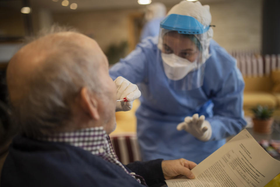 In this photo taken on Wednesday April 1, 2020, aid workers from the Spanish NGO Open Arms carry out coronavirus detection tests on the elderly at a nursing home in Barcelona, Spain. The initiative is part of a clinical trial led by doctors Oriol Mitja and Bonaventura Clotet, from the Lluita Foundation against AIDS and the Germans Trias Hospital, focused on cutting down virus transmission. Spain has seen Thursday a new record in virus-related fatalities that came as the country is seeing the growth of contagion waning, health ministry data showed placing Spain neck to neck with Italy, the country that saw the worst outbreak in Europe. The COVID-19 coronavirus causes mild or moderate symptoms for most people, but for some, especially older adults and people with existing health problems, it can cause more severe illness or death.(AP Photo/Santi Palacios)