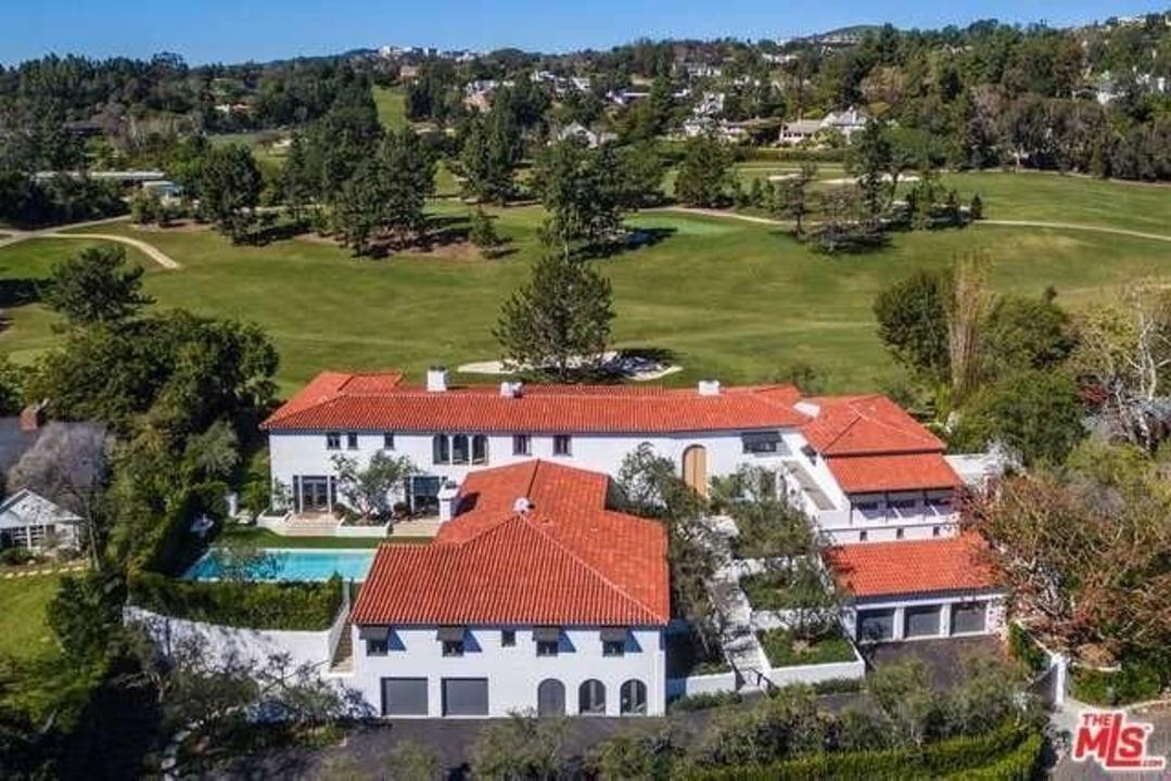 The Mediterranean-style home has striking white walls, a contrasting red roof and enviable golf course views.