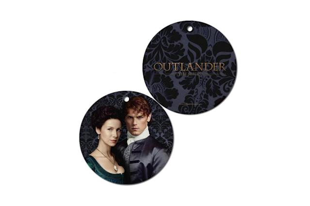 "<p>Theirs is a love that transcends time, so 'tis always the season for this timeless and beautiful ceramic disc featuring the Scottish maverick and his sassenach. <a href=""https://www.outlanderstore.com/products/outlander-jamie-and-claire-ornament"" rel=""nofollow noopener"" target=""_blank"" data-ylk=""slk:Buy here"" class=""link rapid-noclick-resp""><strong>Buy here</strong></a> </p>"