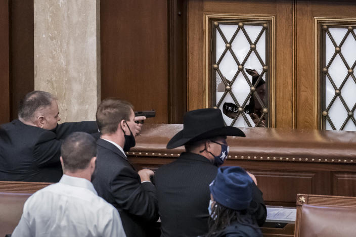 FILE - In this Jan. 6, 2021 file photo, security agents and lawmakers barricade the door to the House chamber as violent mob loyal to President Donald Trump breached the Capitol in Washington. The volume of people inside the Capitol building, along with the lack of arrests made at the time of the riot, has made it difficult to identify people, even with the glut of social media evidence. Federal agents have dug through thousands of social media posts, used sweeping warrants to obtain information on cellphones in the area of the Capitol, facial recognition tools and logs of devices that logged into the congressional WiFi during the riot to try to identify the hundreds of people who stormed the Capitol. (AP Photo/J. Scott Applewhite)