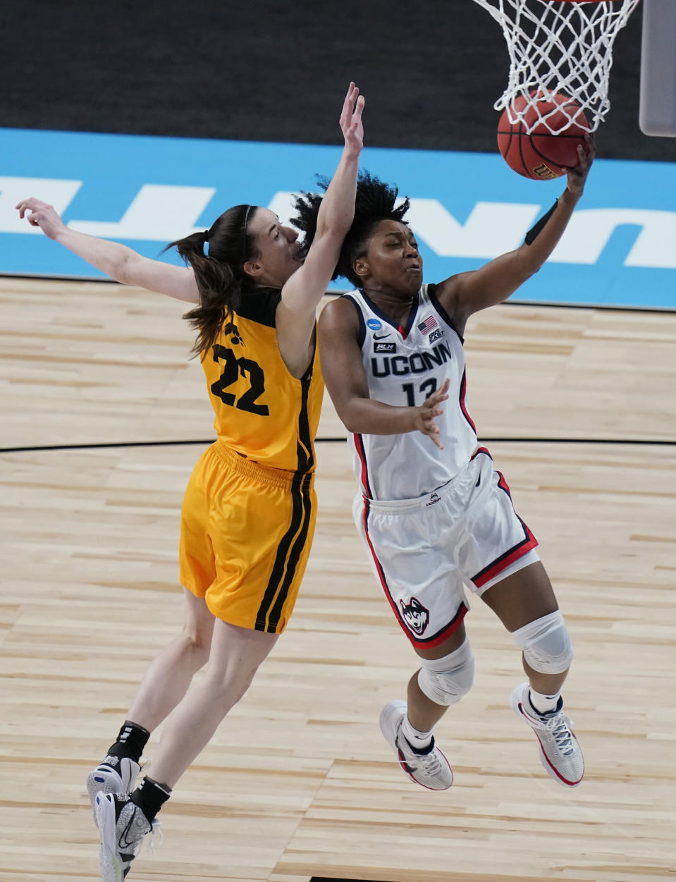 UConn guard Christyn Williams (13) scores past Iowa guard Caitlin Clark (22) during the first half of a college basketball game in the Sweet Sixteen round of the women's NCAA tournament at the Alamodome in San Antonio, Saturday, March 27, 2021. (AP Photo/Eric Gay)