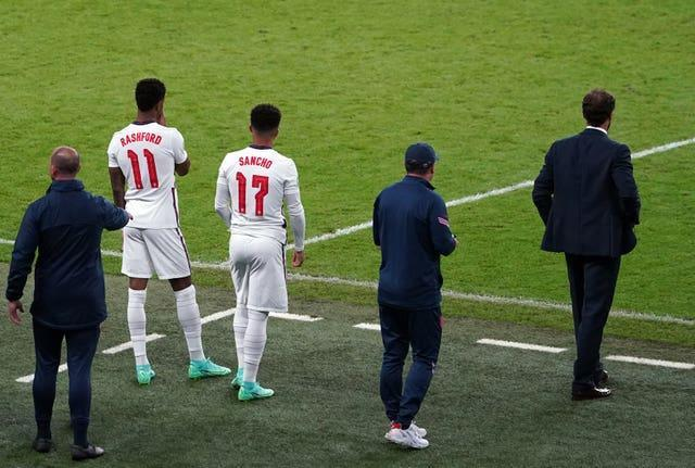 Marcus Rashford, left, and Jadon Sancho wait to come on ahead of Sunday night's shoot-out