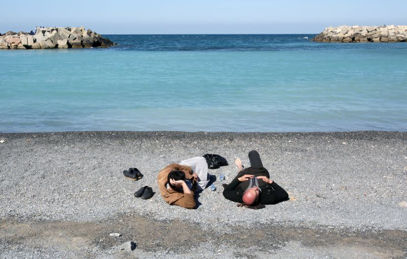 People lay at a beach in Algiers