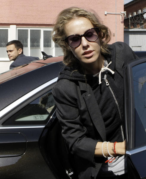 Russian opposition activist and television host Kseniya Sobchak, daughter of the late St. Petersburg mayor Anatoly Sobchak, right, and opposition leader Ilya Yashin, left, exit a car at the headquarters of the Russian Investigation committee in Moscow, Russia, Tuesday June 12, 2012. Russia's top investigation agency has summoned several key opposition figures for questioning in an apparent bid to disrupt the first massive protest against President Vladimir Putin since his inauguration for a third term. (AP Photo/Mikhail Metzel)