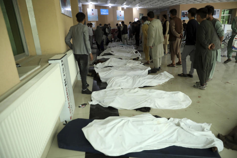 FILE - In this May 8, 2021 file photo, Afghan men try to identify the dead bodies at a hospital after a bomb explosion near a school west of Kabul, Afghanistan. In a report released Monday, July 26, 2021, the United Nations said that more women and children were killed and wounded in Afghanistan in the first half of 2021 than in any year since the UN began keeping count in 2009. (AP Photo/Rahmat Gul, File)