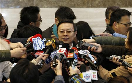 Taiwan's Mainland Affairs Chief Wang is surrounded by microphones and recorders as he talks to journalists at the Shanghai Media Group headquarters in Shanghai