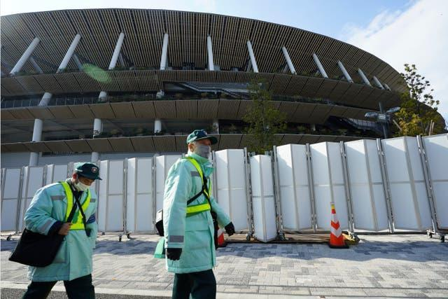 Parking inspectors wearing face masks to protect against the spread of the coronavirus walk past the Japan National Stadium, where opening ceremony and many other events are planned for postponed Tokyo 2020 Olympics