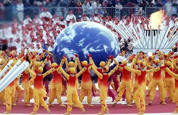 <p>A chorus of Ode to Joy by singers from five continents symbolizes hope for world peace. Anti-land mine activist Chris Moon leads the torch into Olympic Stadium. </p>