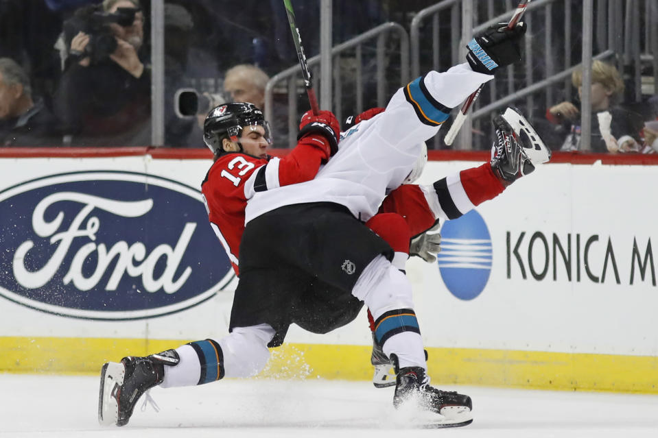 San Jose Sharks center Dylan Gambrell, foreground, sends New Jersey Devils center Nico Hischier (13) to the ice in a collision during the second period of an NHL hockey game, Thursday, Feb. 20, 2020, in Newark, N.J. (AP Photo/Kathy Willens)