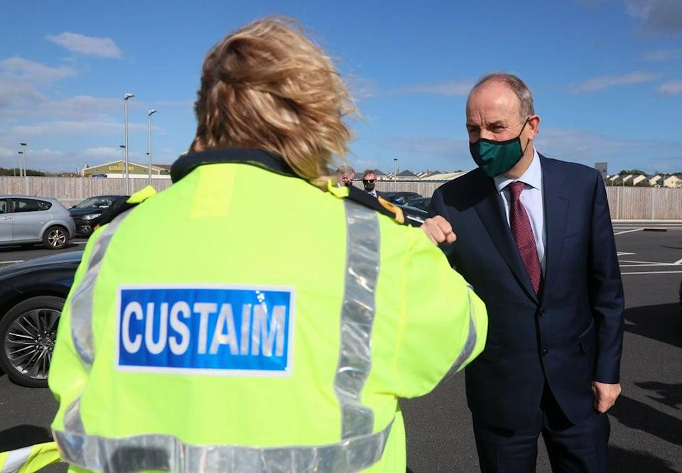 Taoiseach Micheal Martin is greeted by a customs official at Rosslare Europort, Co Wexford (Brian Lawless/PA) (PA Wire)