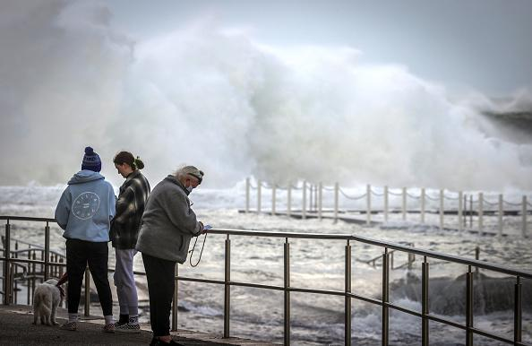 A man wearing a face mask stands in front of large waves at North Narrabeen Beach in Sydney, Australia.