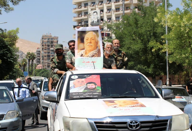 Mourners stand on a back of a vehicle as they hold a picture of Ahmed Jibril, founder of pro-Syrian Palestinian guerrilla faction during his funeral in Damascus