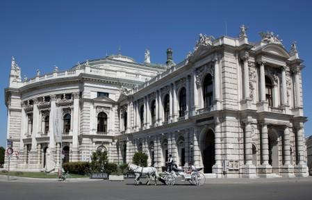A traditional Fiaker horse carriage passes Burgtheater theatre in Vienna