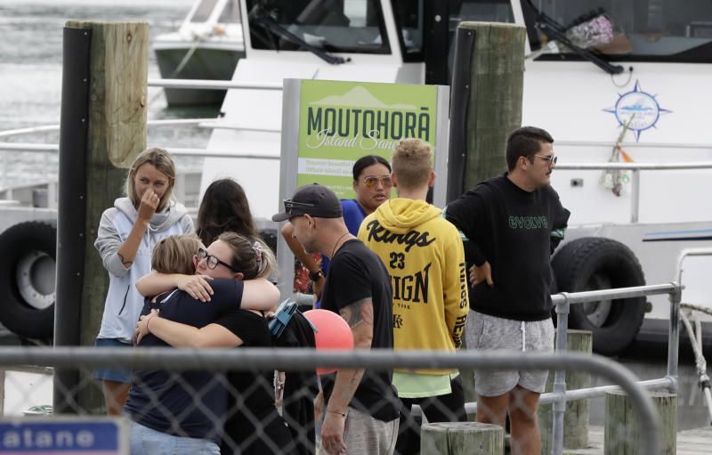 Families of victims embrace as they arrive back to the Whakatane wharf following a blessing at sea on Friday. Source: AP