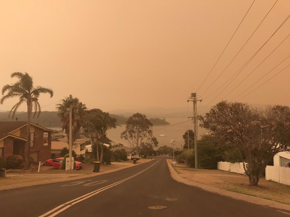 An orange hazy sky is seen over Narooma on Saturday. Source: AAP