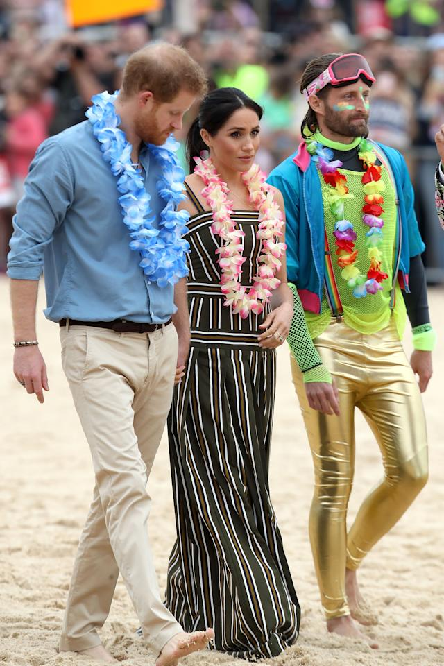"""<p>The honeymooners <a rel=""""nofollow"""" href=""""https://au.lifestyle.yahoo.com/barefoot-meghan-markle-prince-harry-break-royal-protocol-bondi-beach-213835984.html"""">took off their shoes</a> to step onto the sand and were handed floral leis. Photo: Getty </p>"""