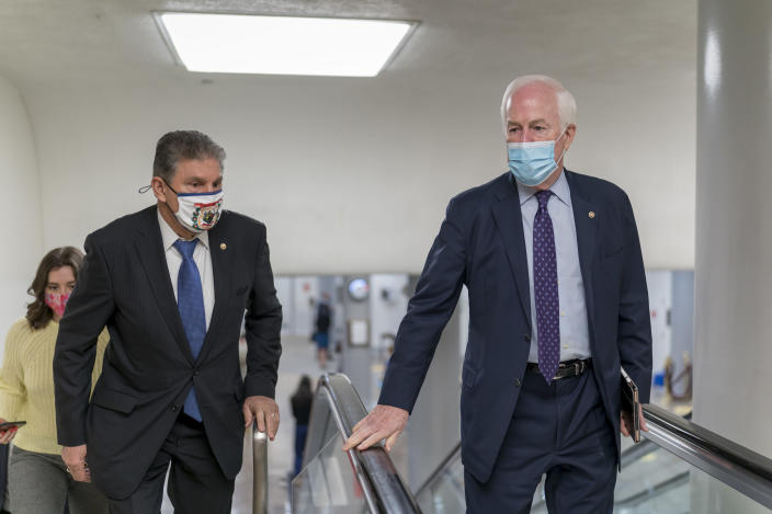 Sen. Joe Manchin, D-W.Va., left, and Sen. John Cornyn, R-Texas, head to the chamber as the Senate steers toward a voting marathon on the Democrats' $1.9 trillion COVID-19 relief bill that's expected to end with the chamber's approval of the measure, at the Capitol in Washington, Friday, March 5, 2021. (AP Photo/J. Scott Applewhite)