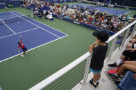Tennis fans watch as Ricardas Berankis, of Lithuania, serves to Diego Schwartzman, of Argentina, during the first round of the US Open tennis championships, Monday, Aug. 30, 2021, in New York. (AP Photo/John Minchillo)
