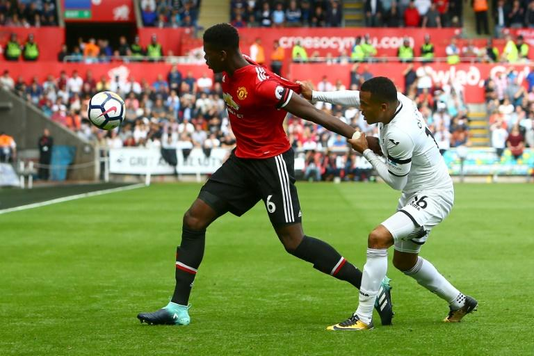 Manchester United's midfielder Paul Pogba's (L) shirt is tugged by Swansea City's defender Martin Olsson during the English Premier League football match August 19, 2017