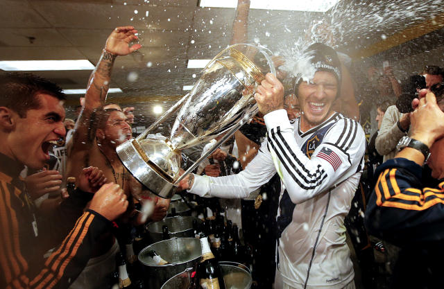 Los Angeles Galaxy's David Beckham, center, of England, is sprayed with champagne as they celebrate in the dressing room after defeating the Houston Dynamo 3-1 in the MLS Cup championship soccer game, Saturday, Dec. 1, 2012, in Carson, Calif. (AP Photo/Jae C. Hong)