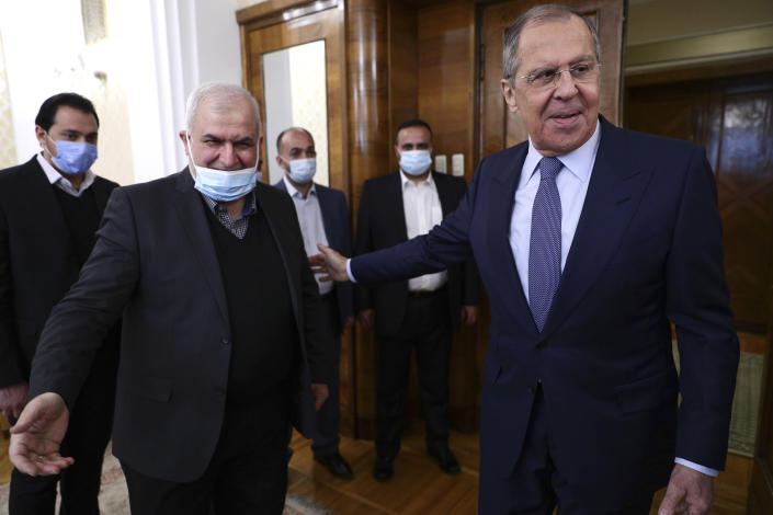 In this photo released by Russian Foreign Ministry Press Service, Russian Foreign Minister Sergey Lavrov, right, welcomes the head of Hezbollah parliamentary bloc Mohamad Raad for talks during their meeting in Moscow, Russia, Monday, March 15, 2021. (Russian Foreign Ministry Press Service via AP)