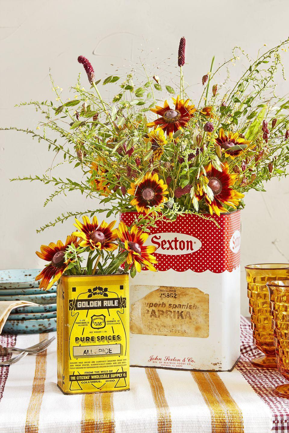 """<p>Decorate your dinner table, dessert display, or kitchen island with these inexpensive arrangements fashioned from wildflowers and spice tins. Feel free to use containers in various heights, sizes, and designs—just be sure they feature autumn's rich reds, bright oranges, and golden hues.</p><p><a class=""""link rapid-noclick-resp"""" href=""""https://go.redirectingat.com?id=74968X1596630&url=https%3A%2F%2Fwww.ebay.com%2Fsch%2Fi.html%3F_from%3DR40%26_trksid%3Dp2380057.m570.l1313.TR0.TRC0.A0.H0.Xspice%2Btin.TRS2%26_nkw%3Dspice%2Btins%26_sacat%3D0&sref=https%3A%2F%2Fwww.countryliving.com%2Fentertaining%2Fg1371%2Fthanksgiving-decorations%2F"""" rel=""""nofollow noopener"""" target=""""_blank"""" data-ylk=""""slk:SHOP SPICE TINS"""">SHOP SPICE TINS</a></p>"""