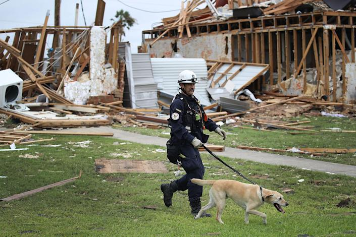 <p>Robert Grant and Rocky from the Texas Task Force 2 search and rescue team work through a destroyed apartment complex trying to find anyone that still may be in the apartment complex after Hurricane Harvey passed through on Aug. 27, 2017 in Rockport, Texas. (Photo: Joe Raedle/Getty Images) </p>