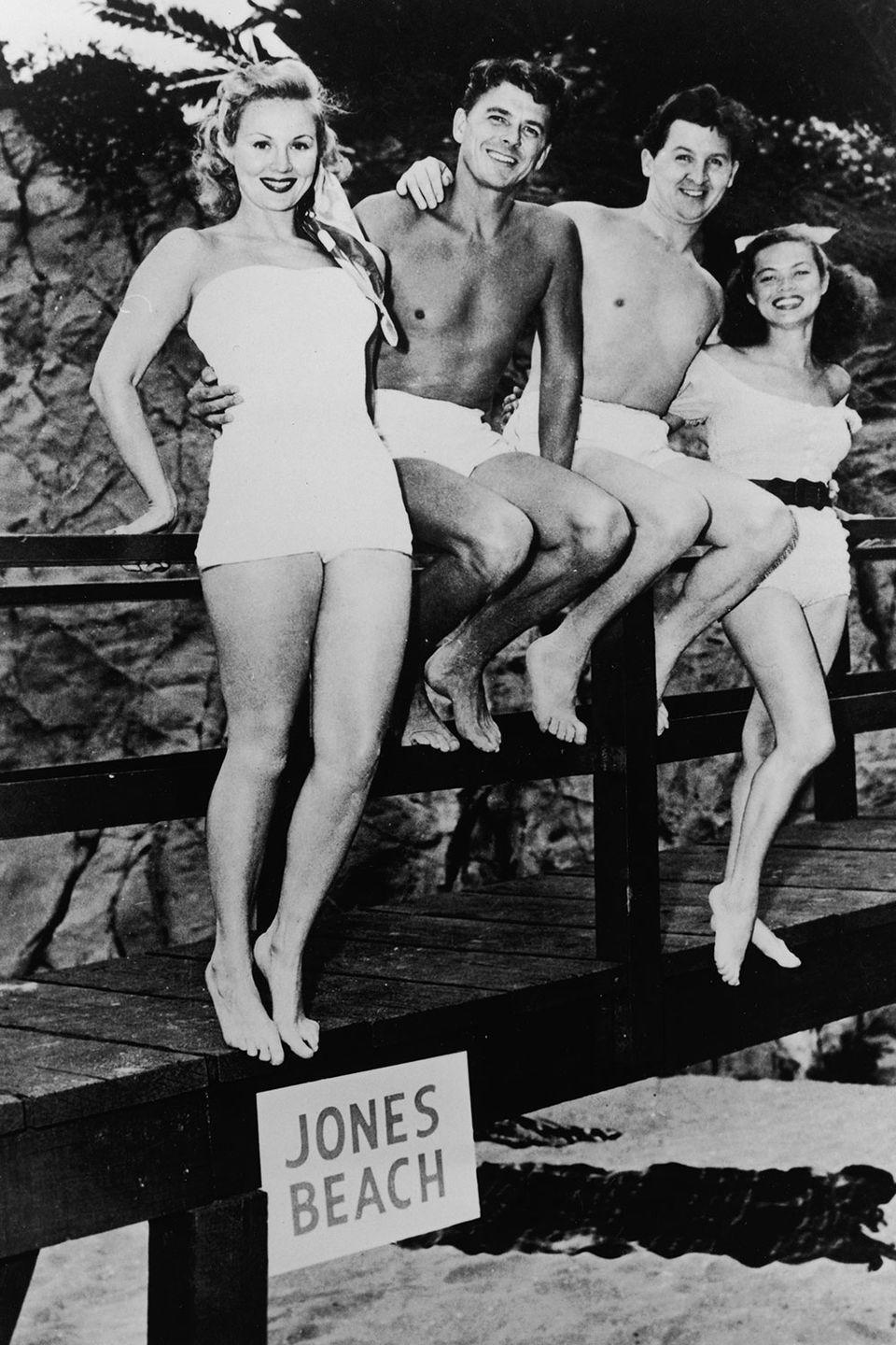 <p>Ronald Reagan sits on the boardwalk with his co-stars in a publicity photo for <em>The Girl From Jones Beach. </em></p>