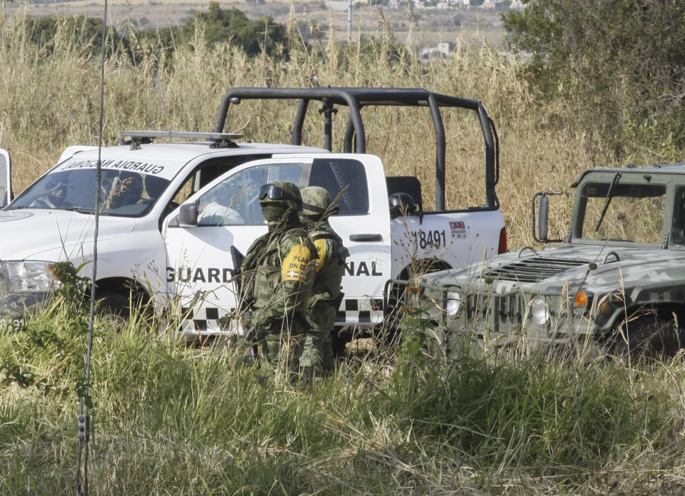 Soldiers stand guard near the site where mass graves were found in Salvatierra, Guanajuato state, Mexico, Thursday, Oct. 29, 2020. A Mexican search group said Wednesday it has found 59 bodies in a series of clandestine burial pits in the north-central state of Guanajuato, and that more could still be excavated. (AP Photo/Mario Armas)