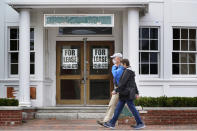 FILE - In this Sept. 2, 2020, file photo, shoppers pass by a former Clark's shoe store that is now one of several vacant retail spaces among the outlet shops in Freeport, Maine. The Labor Department reported unemployment numbers Thursday, Sept. 3. (AP Photo/Robert F. Bukaty, File)
