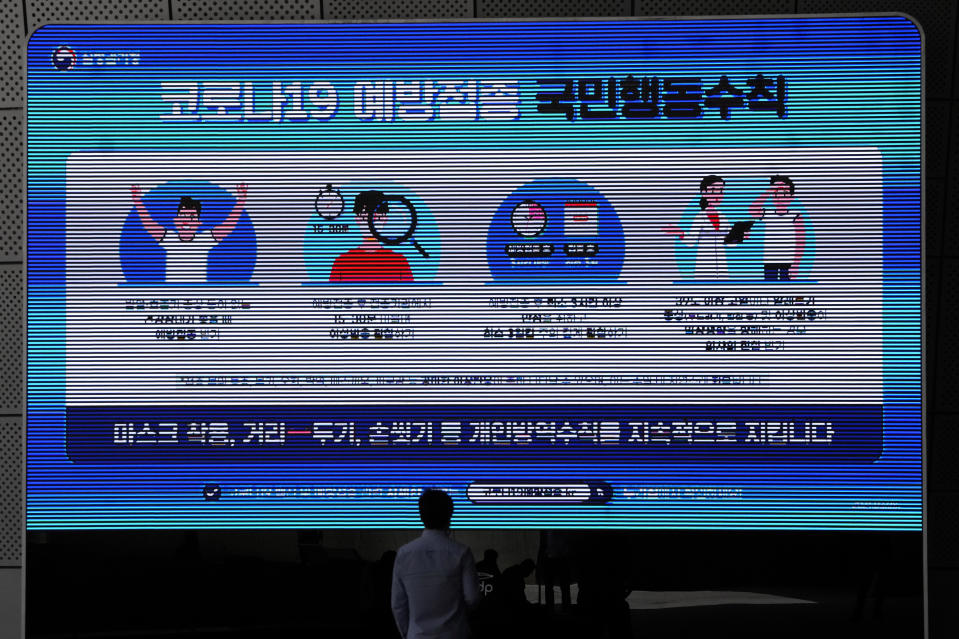 """A man wearing a face mask looks at a screen displaying precautions against the coronavirus in Seoul, South Korea, Monday, May 24, 2021. The letters read """"Keep social distancing and mandatory mask wearing as a prevent the spread of the coronavirus."""" (AP Photo/Lee Jin-man)"""