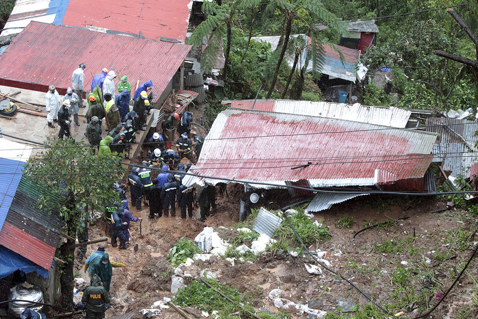 Rescuers search for victims in a house buried by a landslide caused by Tropical Storm Kompasu in Baguio city, northern Philippines on Tuesday Oct. 12, 2021. A number of people have been killed and others were reported missing in landslides and flash flood set off by a storm that barreled through the tip of the northern Philippines overnight then blew away Tuesday, officials said. (AP Photo)