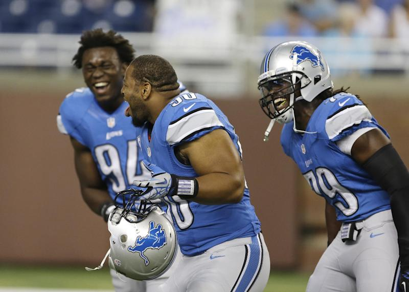 Detroit Lions defensive end Ezekiel Ansah (94), defensive tackle Ndamukong Suh (90) and defensive end Willie Young (79) laugh as players warm up for an NFL football game between the Lions and the Minnesota Vikings in Detroit, Sunday, Sept. 8, 2013. (AP Photo/Carlos Osorio)