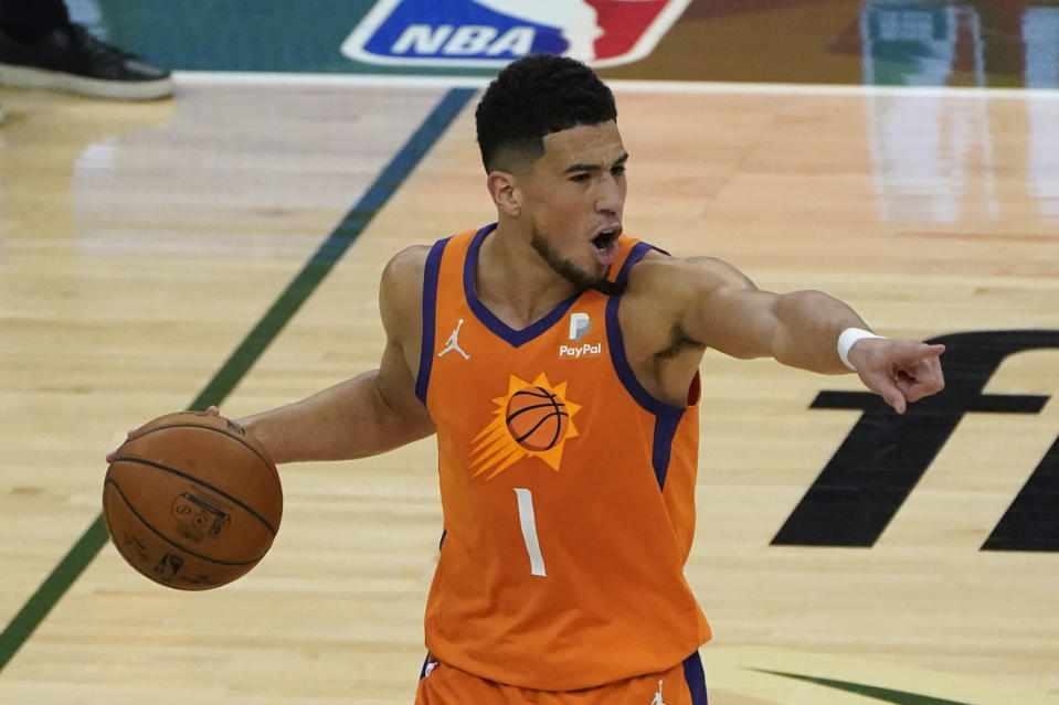 Phoenix Suns guard Devin Booker (1) directs teammates during the first half against the Milwaukee Bucks in Game 4 of basketball's NBA Finals in Milwaukee, Wednesday, July 14, 2021. (AP Photo/Paul Sancya)