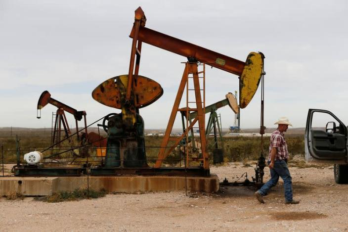 FILE PHOTO: Paul Putnam, 53, a rancher and independent contract pumper walks past a pump jack in Loving County