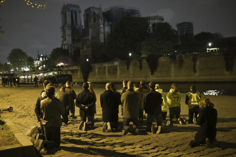 "People pray on their knees by the Seine riverside in front of the Notre Dame cathedral in Paris, Tuesday, April 16, 2019. The inferno that raged through Notre Dame Cathedral for more than 12 hours destroyed its spire and its roof but spared its twin medieval bell towers, and a frantic rescue effort saved the monument's ""most precious treasures,"" including the relic revered as Jesus' Crown of Thorns, officials said Tuesday. (AP Photo/Francisco Seco)"