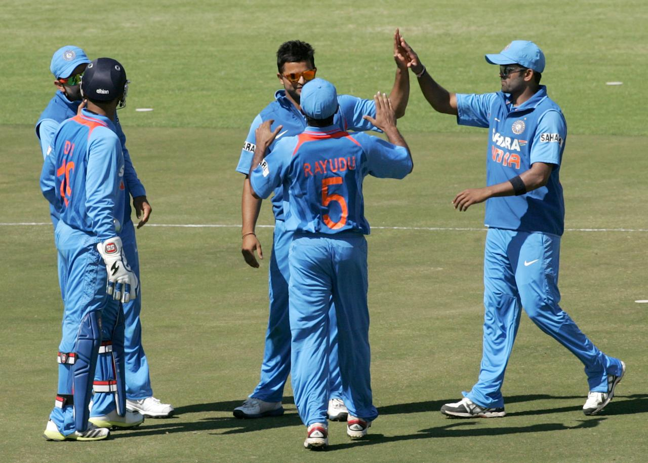 India's Suresh Raina (C) is congratulated by teammates after getting a wicket during the first of the five ODI cricket series matches between India and hosts Zimbabwe at the Harare Sports Club on July 24 2013. AFP/PHOTO Jekesai Njikizana.        (Photo credit should read JEKESAI NJIKIZANA/AFP/Getty Images)