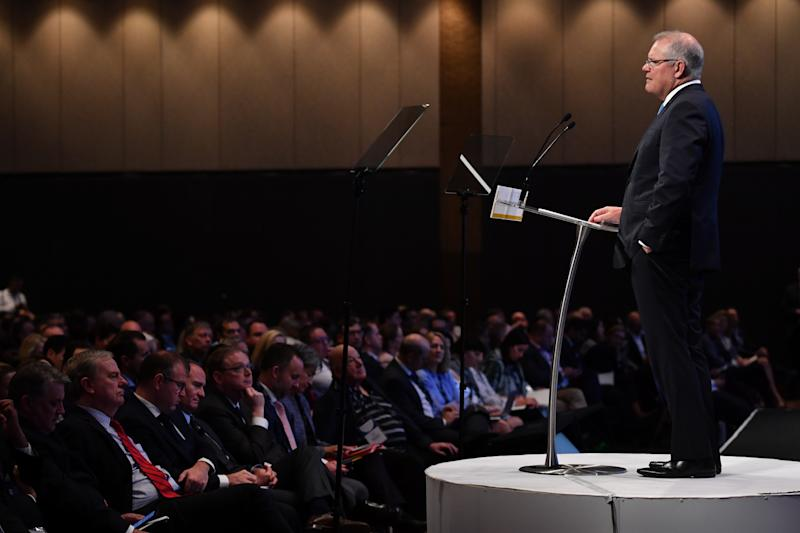 Prime Minister Scott Morrison speaks as former Treasurer Peter Costello (left) listens during the AFR summit in Sydney, Tuesday, March 10, 2020. (AAP Image/Dean Lewins)