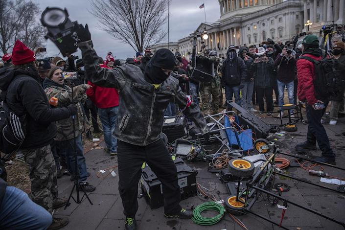 """Demonstrators destroy broadcast video equipment outside the U.S. Capitol building after they earlier stormed the building in Washington, DC, U.S., on Wednesday, Jan. 6, 2021.<span class=""""copyright"""">Victor J. Blue—Bloomberg/Getty Images</span>"""