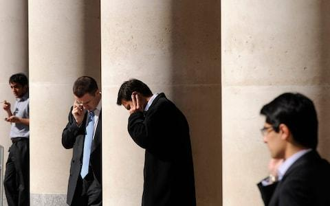 city workers making phone calls outside the London Stock Exchange in Paternoster Square in the City of London - Credit: TOBY MELVILLE/Reuters