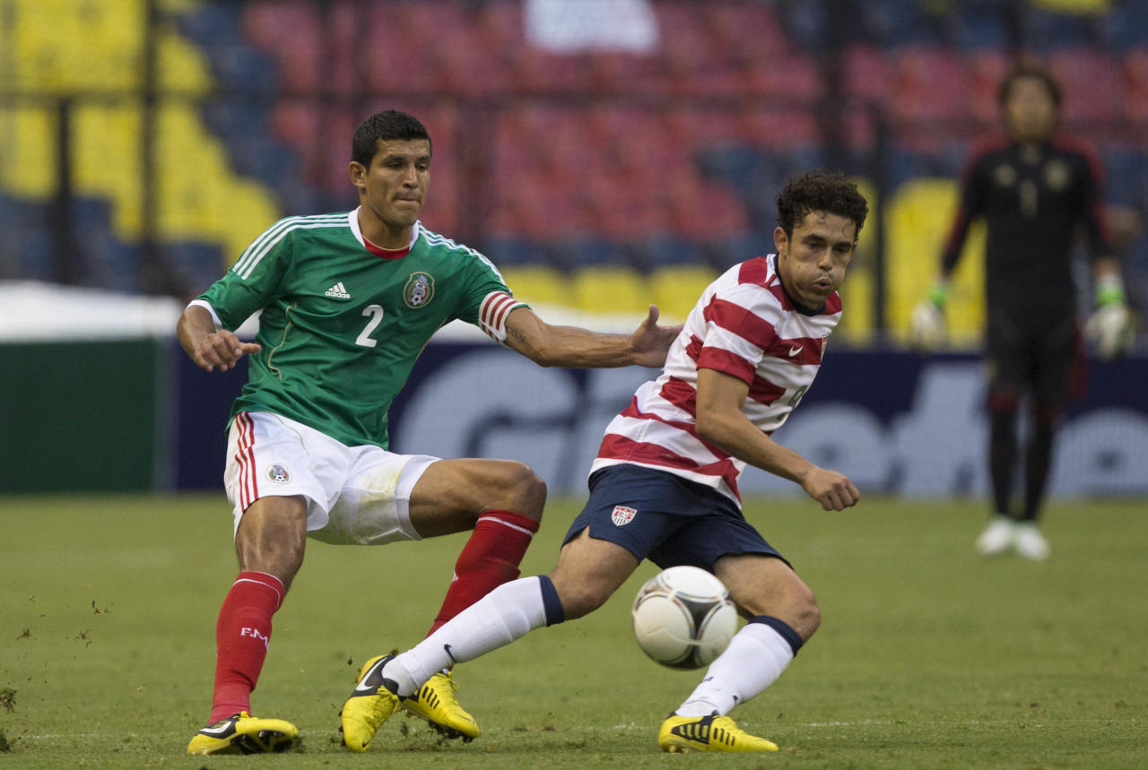 MEXICO CITY, MEXICO - AUGUST 15: Javier Rodriguez  of Mexico fights for the ball with Herculez Gomez of the United States during a FIFA friendly match between Mexico and US at Azteca Stadium on August 15, 2012 in Mexico City, Mexico. (Photo by Miguel Tovar/Getty Images)