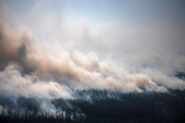 TOPSHOT - This aerial picture taken from an airplane on July 27, 2021, shows the smoke rising from a forest fire outside the village of Berdigestyakh, in the republic of Sakha, Siberia. - Russia is plagued by widespread forest fires, with the Sakha-Yakutia region in Siberia being the worst affected. According to many scientists, Russia -- especially its Siberian and Arctic regions -- is among the countries most exposed to climate change. The country has set numerous records in recent years and in June 2020 registered 38 degrees Celsius (100.4 degrees Fahrenheit) in the town of Verkhoyansk -- the highest temperature recorded above the Arctic circle since measurements began. (Photo by Dimitar DILKOFF / AFP) (Photo by DIMITAR DILKOFF/AFP via Getty Images) (Photo: DIMITAR DILKOFF via AFP via Getty Images)