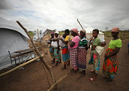 Women and children await medical treatment at a camp for people displaced in flooding in the aftermath of Cyclone Idai, near Beira, Mozambique, March 23, 2019. REUTERS/Mike Hutchings