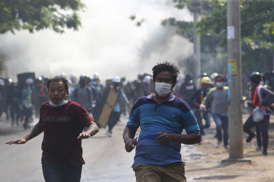 Anti-coup protesters run away when police security forces try to disperse them with tear gas in Mandalay, Myanmar, Saturday, March 13, 2021. Myanmar's military seized power Feb. 1, hours before the seating of a new parliament following election results that were seen as a rebuff to the country's generals. (AP Photo)