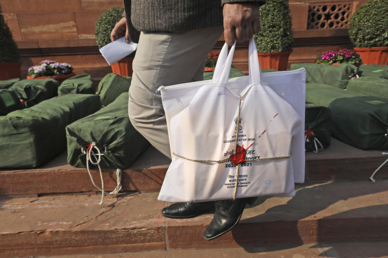 A man carries a bag containing federal budget documents at the parliament house complex in New Delhi, India, Saturday, Feb. 1, 2020. India's Hindu nationalist-led government on Saturday offered relief to taxpayers and vowed to spend billions to double farmers' incomes, upgrade infrastructure, health care and industry to boost the lowest economic growth in a decade. (AP Photo/Manish Swarup)